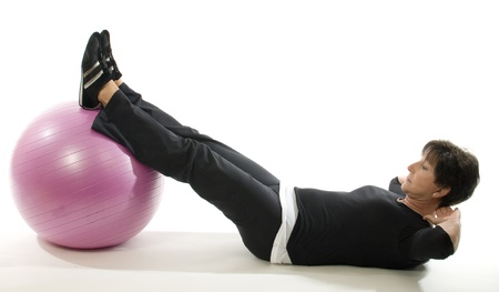 working out: middle age senior woman fitness exercise with core training ball sit ups