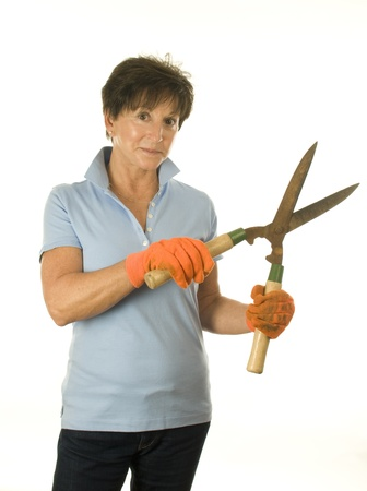trimmer: cute middle age senior female woman gardener smiling with gardening hedge trimmer shears tool Stock Photo