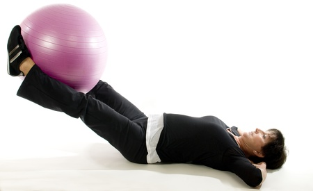 to raise: middle age senior woman exercising leg raise abdominal exercise with core training ball