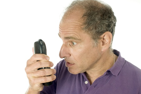 angry middle age senior man telephone with incredulous angry unbelivable emotion look on face photo