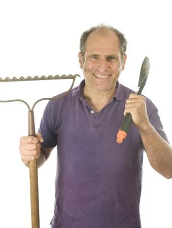 rake: middle age senior man gardener with gardening tools bow rake hand hoe spade