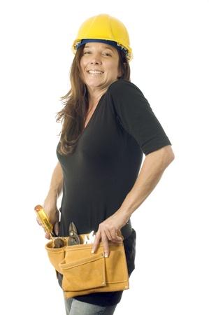 aantrekkelijke vrouwelijke bouwer aannemer timmerman met gereedschapsriem gereedschap en beschermende helm helm Stockfoto
