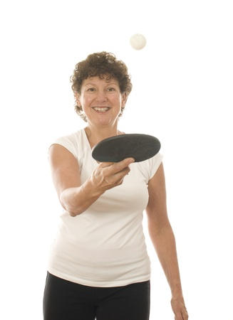 table tennis: middle age active fit senior woman playing ping pong with table tennis paddle and ball Stock Photo