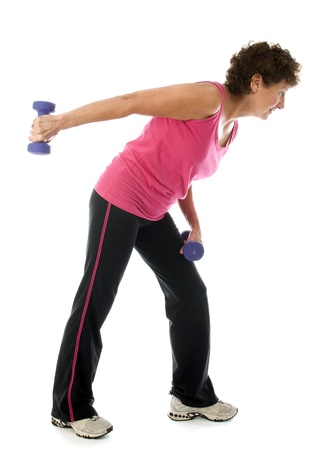 senior exercising: happy middle age senior woman exercising with dumbbells doing tricep shoulder raise