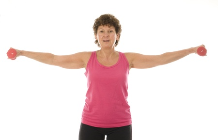 woman lifting weights: middle age senior woman fitness exercising shoulder raise strength training with dumbbell weights