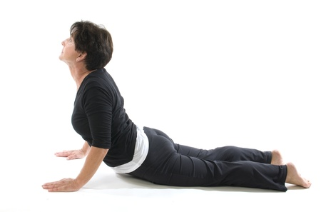 woman middle age: middle age senior woman yoga exercise cobra position elbow press