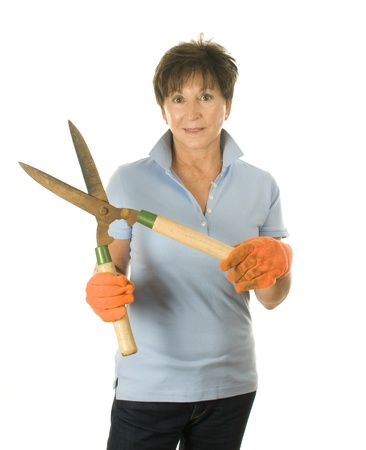 babyboomer: cute middle age senior woman garden gloves and hand tool hedge trimmer shears Stock Photo
