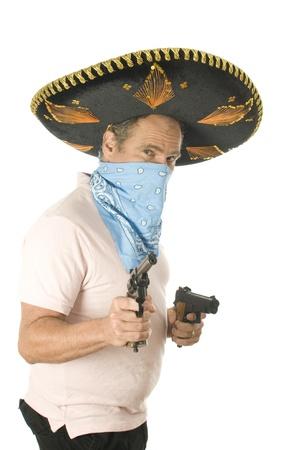 middle age senior tourist male wearing Mexican sombrero Mariachi hat  cowboy bandana handgun pistols photo