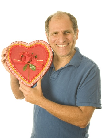 smiing: middle age senior man heart shaped love box of  Valentines day chocolate candy for wife or girlfriend
