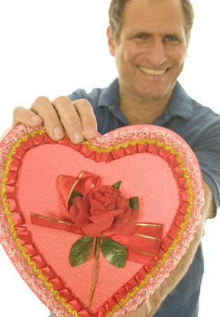 smiing: middle age senior man offering heart shaped love box of  Valentine Stock Photo