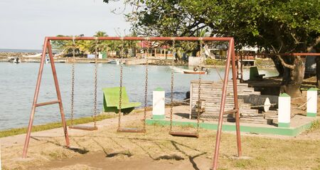 corn island: childrens park swing set old fashioned waterfront Brig Bay Corn Island Nicaragua Stock Photo