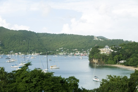 grenadines: Port Elizabeth harbor with yachts sail boats tankers with view of Hamilton residences Princess Margaret Beach Bequia St. Vincent and The Grenadines in Caribbean Sea