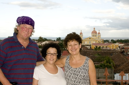 middle america: middle age tourists on La Merced Church with view Cathedral of Granada Nicaragua Central America Spanish tile rooftops panorama