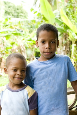 nicaragua: two young children brothers smiling portrait with jungle tropical plants in background Big Corn Island Nicaragua Central America