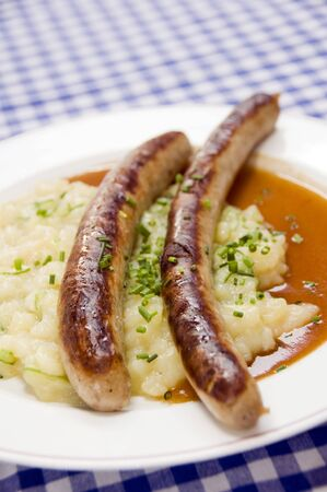 bratwurst: German thuringian sausage thuringer rostbratwurst with potato cucumber salad as photographed in Berlin Germany Stock Photo