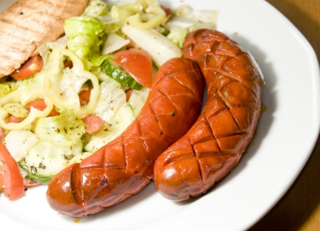 debrecziner spicy Hungarian sausage with salad as photographed in Budapest Hungary