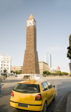 taxi famous building: Clock Tower ave Habib Bourguiba Ville Nouvelle Tunis Tunisia Africa yellow taxi cab