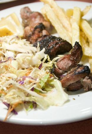 pork and liver kabob shish kabab meal salad French fried potatoes as photographed in Tunis Tunisia