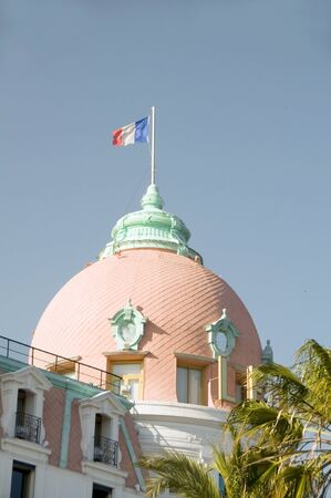 d'azur: classic architecture historic famous hotel Nice France on French Riviera Cote dAzur with national flag
