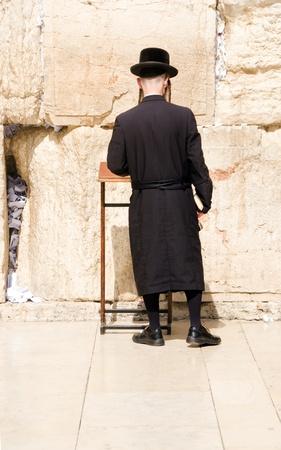 religious clothing: Hasidic Chassidic Jews wearing traditional clothing praying at The Western Wall Jerusalem Israel Palestine