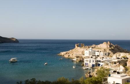 fisherman houses built into rock cliffs on Mediterranean Sea Firopotamos harbor Milos Cyclades Greek Island Greece with Greek church photo