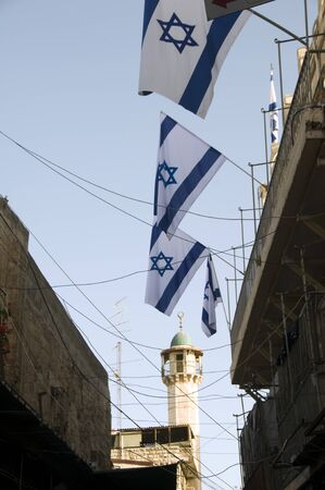 flags of Israel in Jerusalem Palestine old city market with mosque minaret in background Imagens - 14787712