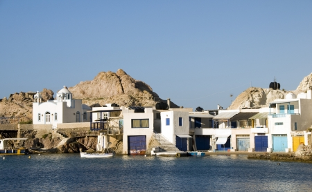 fisherman houses built into rock cliffs on Mediterranean Sea Firopotamos Milos Cyclades Greek Island Greece photo