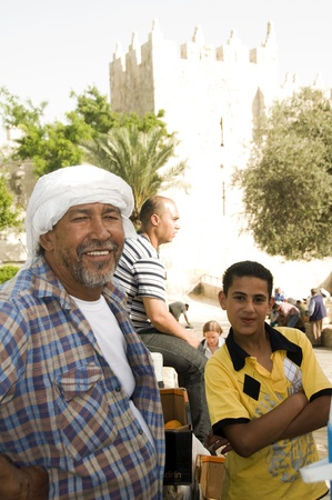Jerusalem-May 26  A Palestinian juice vendor man and his helper son are smiling at tourists in front of the Damascus Gate to the Old City in Jerusalem, Palestine, Israel on May 26, 2012