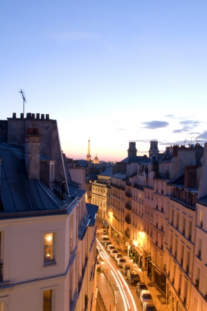 night scene with car movement light streaks Rue de Vaugirard rooftops of Paris France Europe residential neighborhood Latin Quarter with view of Eiffel Tower and Dome of Invalides photo