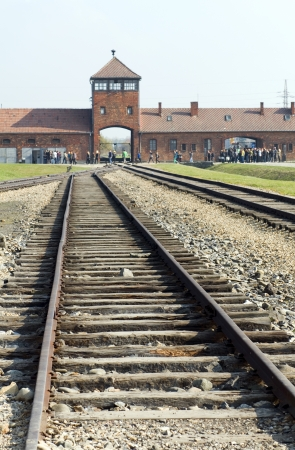 concentration camp: Birkenau, Poland-October 15, 2013: The infamous iconic train tracks and entry gate building where prisoners arrived at Birkenau German Nazi Concentration death camp Poland to be divided into those who would live and those who would die immediately as seen