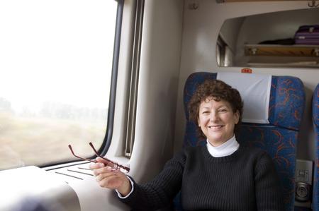Feliz jubilado mayor edad media femenina en el tren de primera clase en Polonia Europa turismo Foto de archivo - 26609625