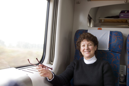 happy female retired middle age senior on first class train in Poland Europe tourism