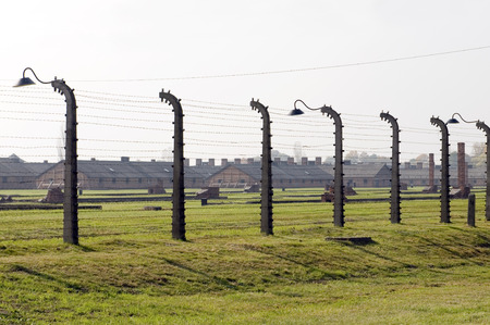 concentration camp: poles and barbed wire fence surrounding Auschwitz concentration camp Poland with barracks in background built by Nazi Germany