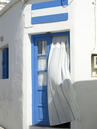 breeze: typical old fashioned Greek Island house door with curtain Kimilos Greece Cyclades