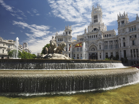 City hall  Palace Cybele Palacio de Cibelas with statue and fountain Madrid Spain with national flags flying Редакционное