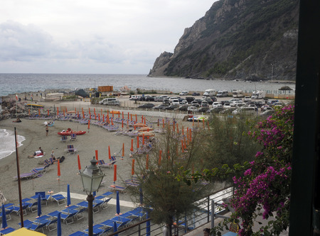 MONTEROSSO, ITALY-OCT. 24:  The beach with tourists is seen in Monterosso, Italy, Europe with the cliffs of Cinque Terre in background on the Mediterranean Ligurian Sea on October 24, 2015. Редакционное
