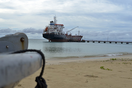 oil tanker vessel at dock with boat bow in foreground with anchor pulley Picnic Center Beach Big Corn Island Nicaragua Central America