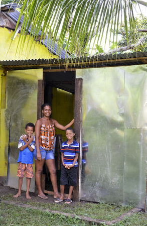 corn island: BIG CORN ISLAND, NICARAGUA-NOV. 16: A proud young mother and two boys are seen by new zinc sheet metal house in jungle in Big Corn Island, Nicaragua, Central America on November 16, 2015.
