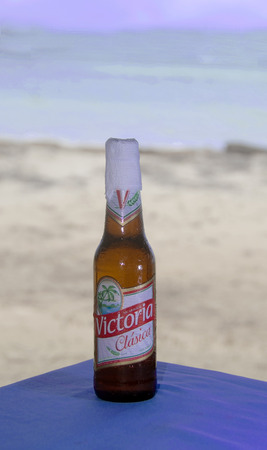 CORN ISLAND,NICARAGUA-JANUARY 15: A bottle of the national beer of Victoria Clasica is shown as served with napkin wrapped around end with beach background Big Corn Island, Nicaragua, Central America on January 15, 2017.