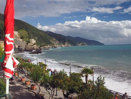 MONTEROSSO, ITALY-SEPT. 22: Tourists walk the tree lined promenade over the  Mediterranean Sea in Monterosso in Cinque Terre, Italy with old town in the distance on the mountain of September 22, 2016.