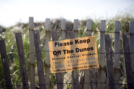 MONTAUK, NEW YORK-JUNE 8: First Coastal erosion control project sign to keep off dunes is seen on beach in Montauk, New York, The Hamptons on June 8, 2018.