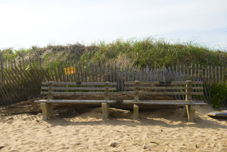 Surfers The Bench on Ditch Plains Beach Montauk, New York, The Hamptons with erosion control sign on dunes Фото со стока