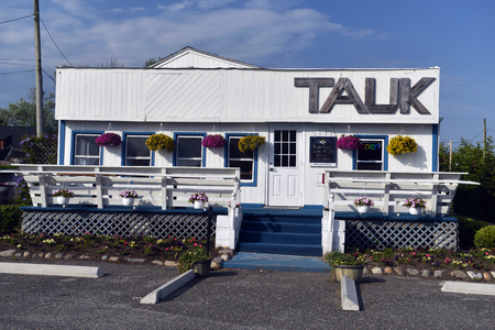 MONTAUK, NEW YORK-JUNE 8: TAUK restaurant, the new name of one of the oldest restaurants in Montauk, New York, The Trail, is seen on June 8, 2018. Фото со стока
