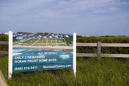 MONTAUK, NEW YORK-JUNE 8: Sign showing oceanfront lots for sale for millions of dollars on Ditch Plains Beach, Montauk, New York, The Hamtpons on June 8, 2018. Фото со стока