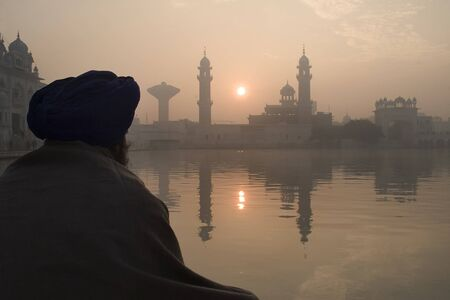 sikhism: View of the golden temple with a man in meditation, Amritsar, India