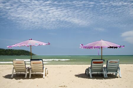 two pink umbrellas and white sand at a Phuket beach, Thailand