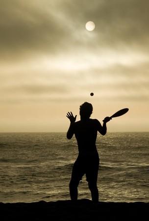 young man playing beach tennis Stock Photo