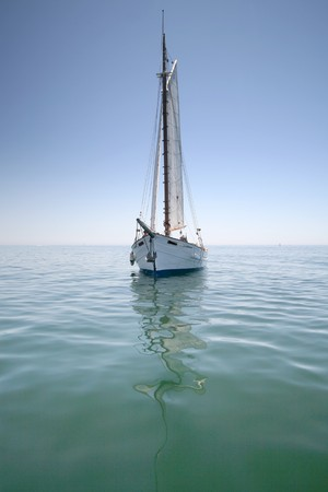 Sailboat sailing in the morning with blue cloudy sky Stock Photo
