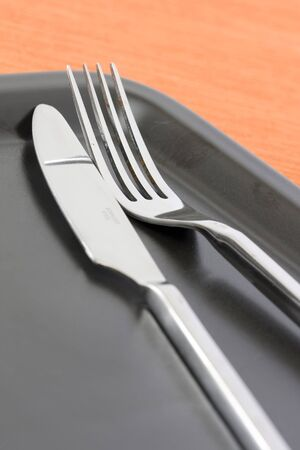 detail of a knife and fork at a black dinner plate with a orange backgound Stock Photo - 4263769