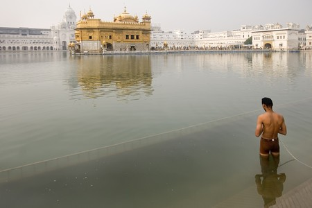 amritsar: View of the golden temple with a man in meditation, Amritsar, India
